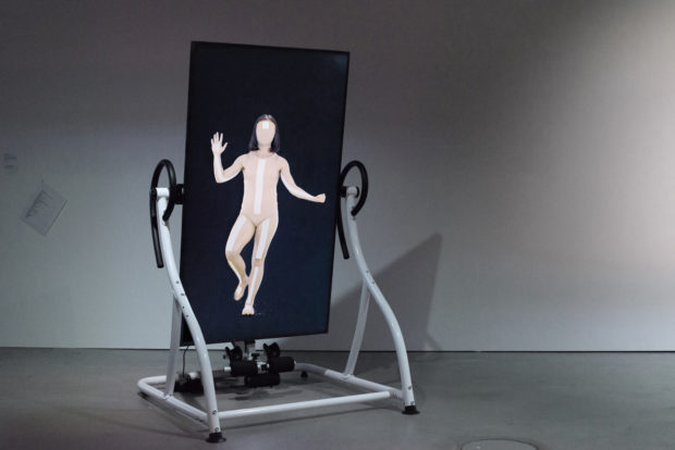 Coralie Vogelaar, Infinite Posture Dataset, video installation with a motorised Relax Zone Pro Inversion Table, 2020. Dancer: Courtney May Robertson, Choreography i.c.w Marjolein Vogels. Installation shot at HeK (House of electronic Arts) Basel